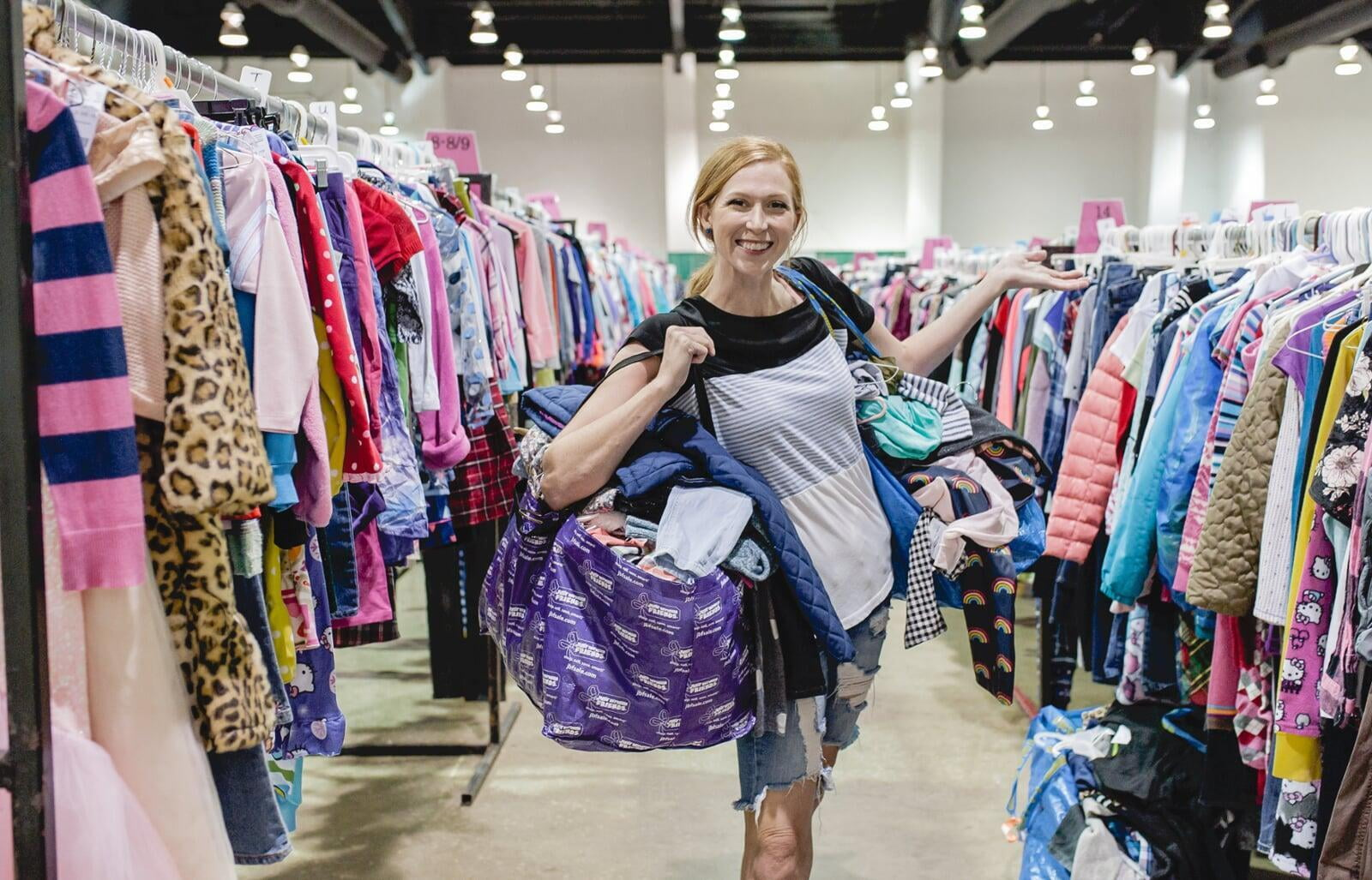 Mom holds hand up to show of rows and rows of clothing for sale at 50 to 90% off retail prices!