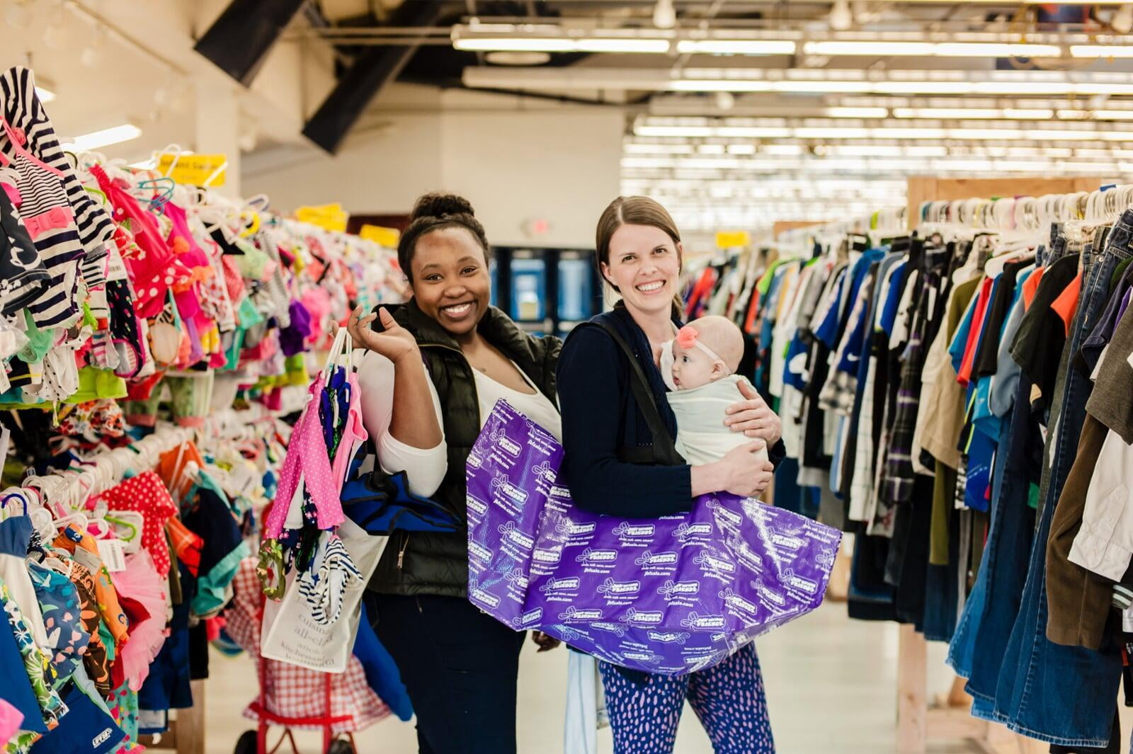 Two friends shop together—one mom wears her baby girl—as they find great deals at their local JBF sale.