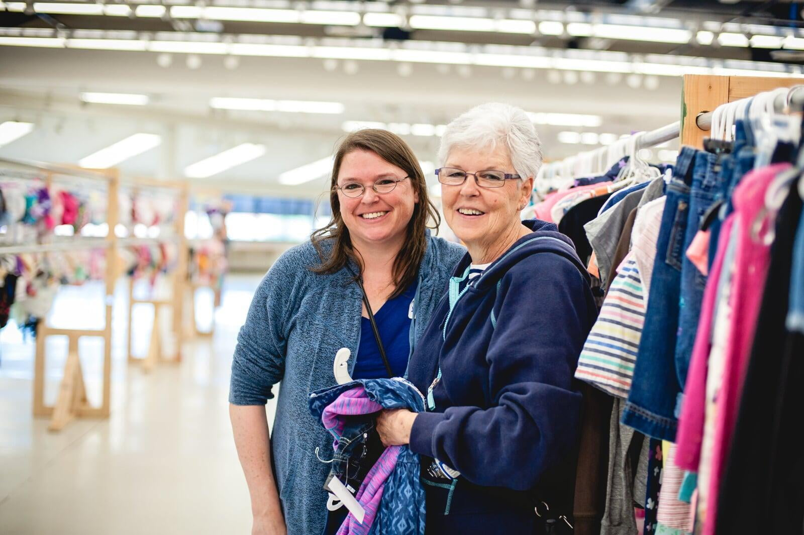 A mom and grandmother stand beside a rack of clothing at a JBF sale in Texas.